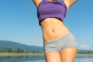 Closeup of young fit woman's belly outdoors in summer. Fitness girl in gray shorts and purple tank top outdoors at the beach on sunny summer day. No retouch, developed from RAW, vibrant colors, natural light.